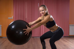 Woman in Squat Position Holding Fitness Ball Stock Photo