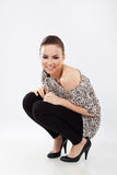 Woman in squat position smiling Royalty Free Stock Photo