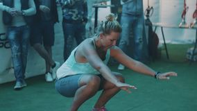 Woman squats while balancing board on a cylinder during festival competition. Woman squats while balancing board on a cylinder during festival event. Changing stock footage