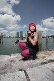Woman squatting by the bay Stock Images