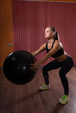 Woman in Squatting Position Holding Exercise Ball Stock Photo