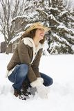 Woman squatting in snow. Stock Photos