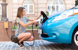 Woman squatting to plug her eco car Stock Photography