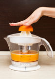 A woman squeezes orange juice in kitchen. A woman squeezes orange juice Royalty Free Stock Image
