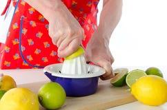Woman squeezing half a lemon Stock Photography