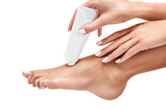 Woman squeezing moisturising cream on her leg. Woman squeezing moisturising cream on her leg over white background. Healthy feet concept Royalty Free Stock Image