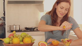 Woman squeezing orange over her fruit salad Royalty Free Stock Photography