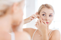 Woman squeezing pimple at bathroom mirror Stock Photo