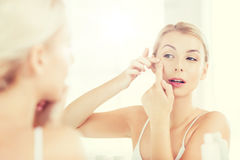 Woman squeezing pimple at bathroom mirror. Beauty, hygiene, skin problem and people concept - young woman looking to mirror and squeezing pimple at home bathroom stock photo