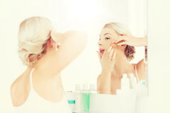 Woman squeezing pimple at bathroom mirror royalty free stock photography