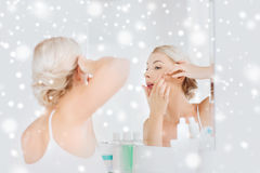 Woman squeezing pimple at bathroom mirror royalty free stock photo
