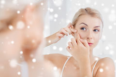 Woman squeezing pimple at bathroom mirror royalty free stock image