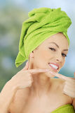 Woman squeezing pimple on cheek. Royalty Free Stock Image