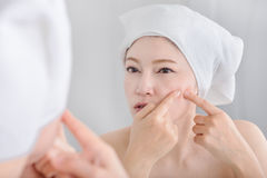 Woman squeezing pimple in front of mirror Royalty Free Stock Photo