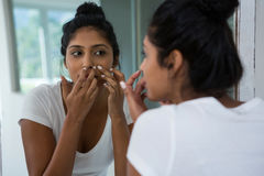 Woman squeezing pimple reflecting on mirror. In bathroom at home stock photos
