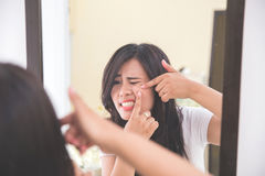 Woman squeezing pimples look at the mirror Stock Photos