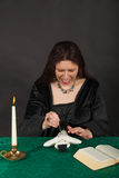 A woman is stabbing a doll with a needle Stock Photography