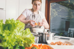 Woman stabs the eggs into the bowl to make a cake. Stock Images