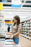 Woman with stack of books in store stock photography