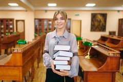 Woman with stack of books in university library. Young woman with stack of books in reading room, university library. Female person in knowledge depository stock images