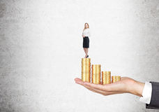 Woman on a stack of coins Stock Photography