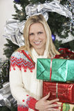 Woman With Stack Of Gifts Against Decorated Christmas Tree Stock Photo