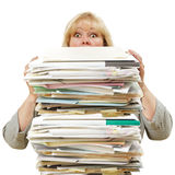 Woman with stack of papers. Mature woman almost buried by a mountain of paperwork Royalty Free Stock Photos