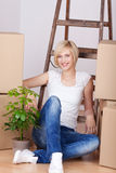 Woman With Stacked Cardboard Boxes Sitting On Floor Royalty Free Stock Photography