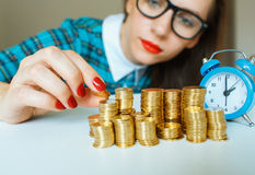 Woman stacking gold coins into  columns Stock Photo