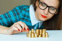 Woman stacking gold coins into  columns Royalty Free Stock Photo