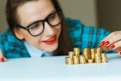 Woman stacking gold coins into  columns Stock Image