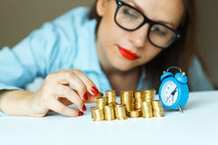 Woman stacking gold coins into  columns Stock Photos