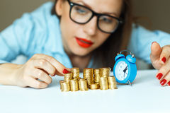Woman stacking gold coins into  columns Royalty Free Stock Photos