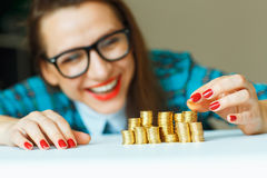 Woman stacking gold coins into increasing columns Stock Image