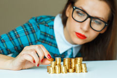 Woman stacking gold coins into increasing columns Royalty Free Stock Photo