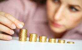 Woman stacking gold coins into increasing columns Royalty Free Stock Image