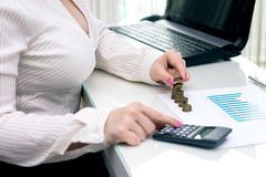 Woman stacks coins. Counting every penny. Royalty Free Stock Images