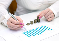 Woman stacks coins. Counting every penny. Stock Photography
