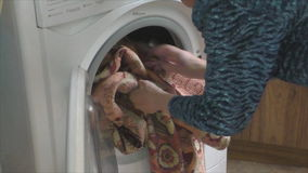 Woman stacks dirty linen in the washing machine stock footage