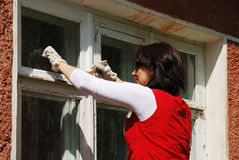 Woman staining window on the outside. Royalty Free Stock Photos