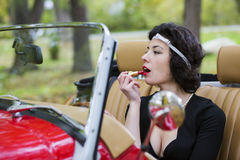 Woman stains the lips before car mirror Royalty Free Stock Image