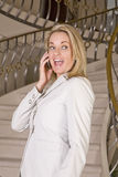 Woman on stairs laughing on phone Stock Photography