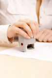 Woman stamping a document. Royalty Free Stock Image