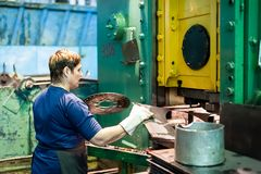 Woman stamps details on hydraulic press Stock Image