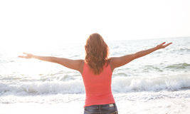 Woman stand on beach with arms open Stock Photos