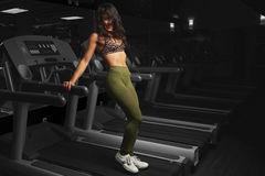 Woman stand on cardio machine. In indoor gym Royalty Free Stock Image