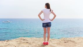 Woman stand at edge of cliff on sunny day in slow motion. Carefree female look at view of blue sea. Smiling young woman in white t-shirt standing at edge of stock footage