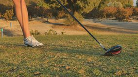 Woman hit the ball with golf club. Woman stand at green golf course and training to hit the ball. Close-up shot. Shooting from down. Female beats the ball with stock video footage