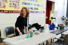 Local school district art fair. A woman at a stand at a local school district art fair royalty free stock photos