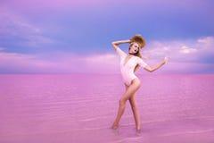 Beautiful top model posing in pink lake. Charming super model posing with hat in fantastic pink lake Royalty Free Stock Images